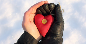 heart symbol in hands of one of them in a black glove