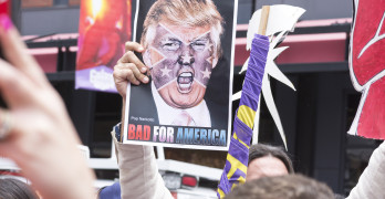 "SAN DIEGO USA - MAY 27 2016: A protester holds a sign featuring an angry photo of Donald Trump and reading ""Bad for America"" at an anti-Trump protest outside a Trump rally in San Diego."