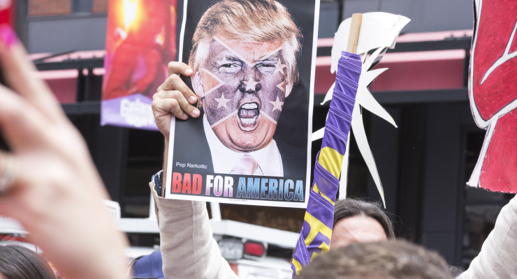 """SAN DIEGO USA - MAY 27 2016: A protester holds a sign featuring an angry photo of Donald Trump and reading """"Bad for America"""" at an anti-Trump protest outside a Trump rally in San Diego."""