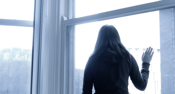 A monochromatic image of a faceless girl in black looking hopelessly out a window. Good for use with themes relating to depression or despair. ** Note: Slight blurriness, best at smaller sizes