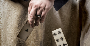 Man smoking a cigar and playing poker with falling cards
