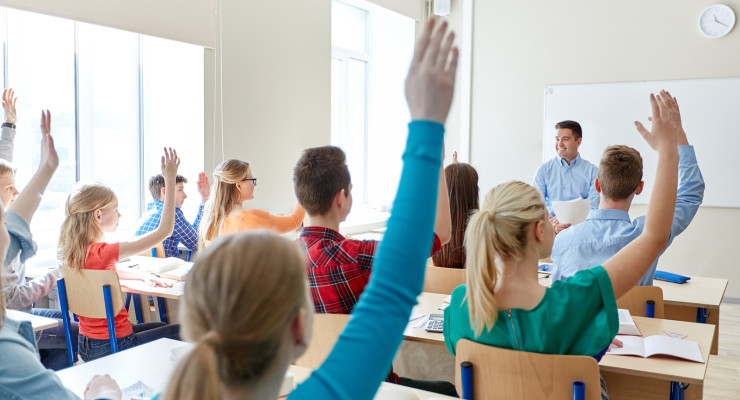education, high school, teaching, learning and people concept - group of happy students raising hands and teacher in classroom
